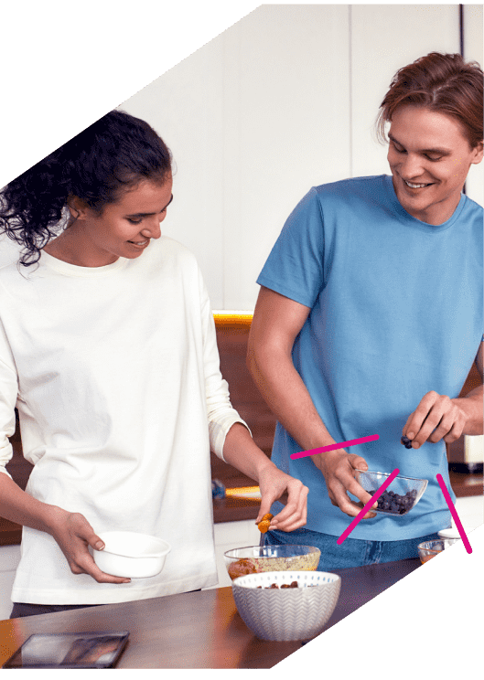 a man and woman making breakfast with oats
