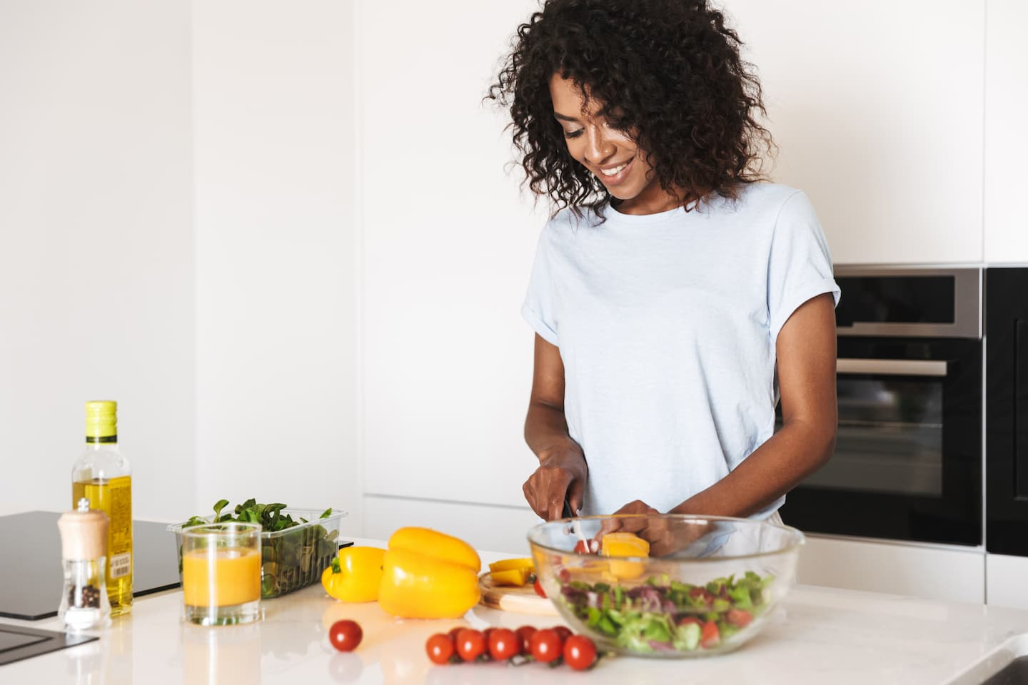 woman cutting up vegetable in a home kitchen