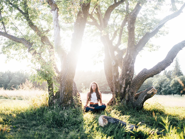 woman meditating between 2 trees